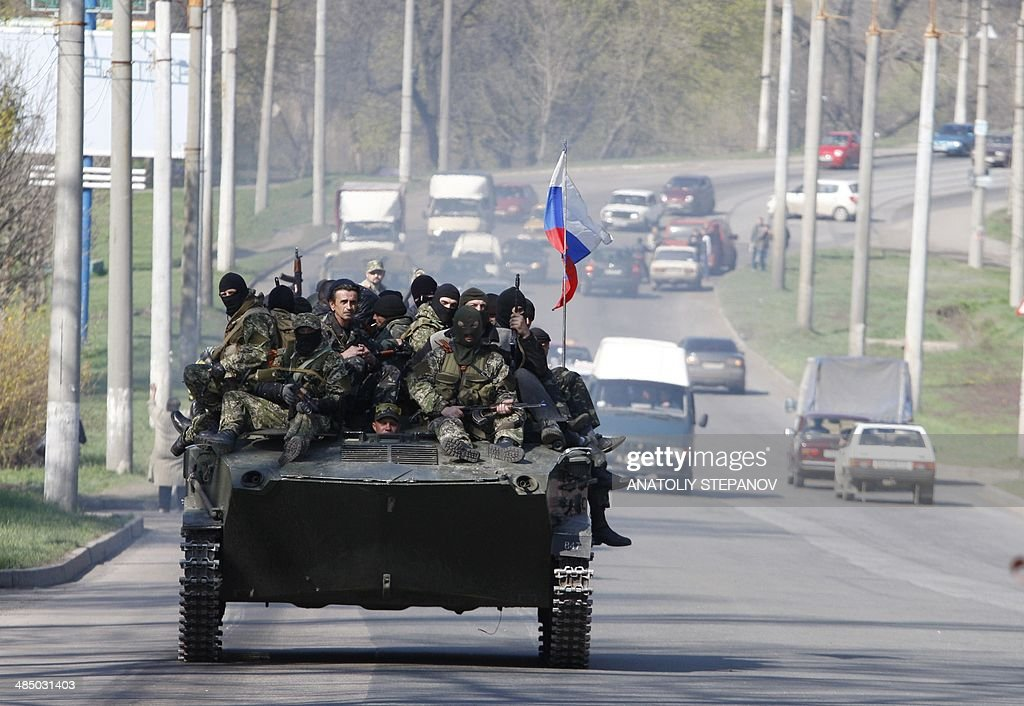 Pro-Russians wearing military fatigues ride on an armoured personnel carrier (APC) seized to the Ukrainian army in the eastern Ukrainian city of Kramatorsk on April 16, 2014. Russian leader Vladimir Putin warned that Ukraine is on the verge of civil war, the Kremlin said Wednesday, after the Kiev government sent in troops against pro-Moscow separatists in the east of the country.