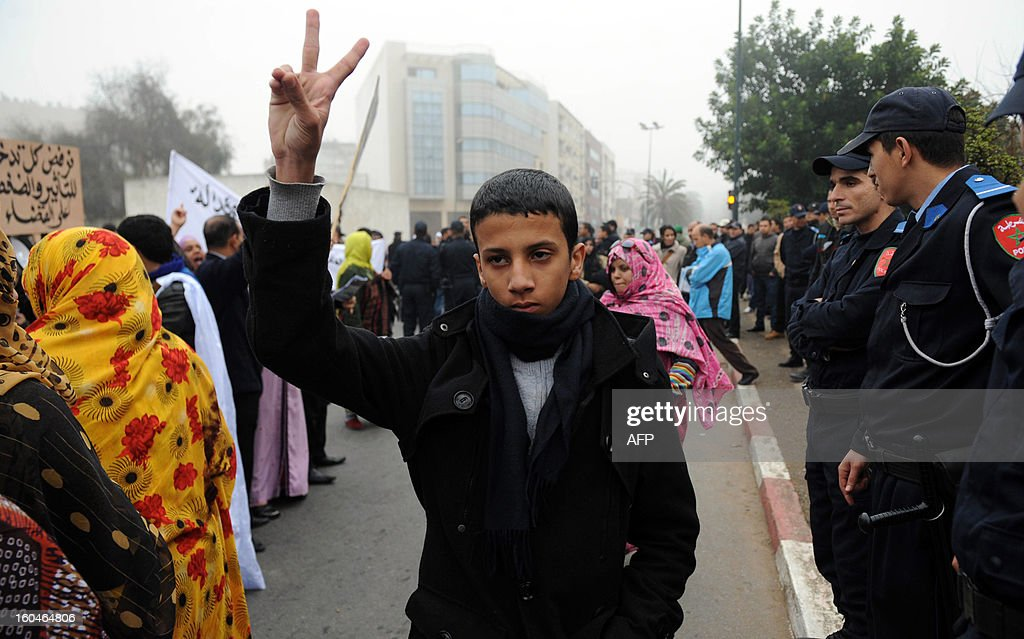 A pro-Sahrawi activist flashes the victory sign in front of the court in Rabat, on February 1, 2013. Rival protests were held outside a military tribunal in the Moroccan capital where 24 Sahrawis accused of killing members of the security forces in the Western Sahara in 2010 are being tried.