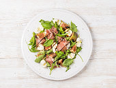 Prosciutto, arugula, basil, figs and mozzarella salad over white wooden background, top view