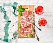 Prosciutto di Parma ham slices and fresh basil leaves on wooden board and rose wine glasses over white painted wooden background, top view, horizontal composition