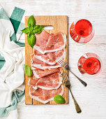 Prosciutto di Parma ham slices and fresh basil leaves on wooden board and rose wine glasses over white painted wooden background, top view