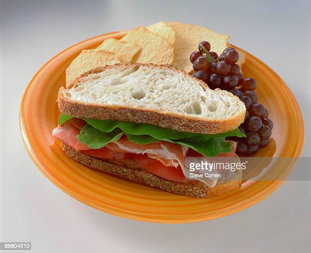 Prosciutto sandwich with chips and grapes