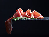 prosciutto with rosemary on a black reflective background