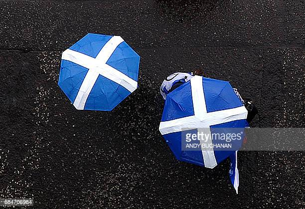 ProScottish Independence supporters march with Scottish Saltire umbrellas with others toward George Square for a rally in Glasgow Scotland on July 30...