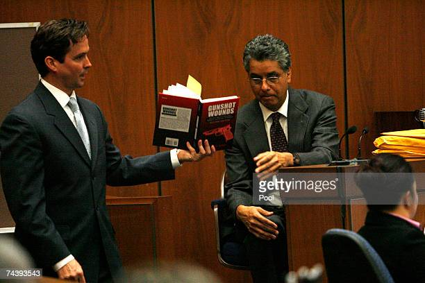 Prosecutor Alan Jackson shows the book 'Gunshot Wounds' to prosecution witness Dr Louis Pena during the afternoon session of the murder trial of...