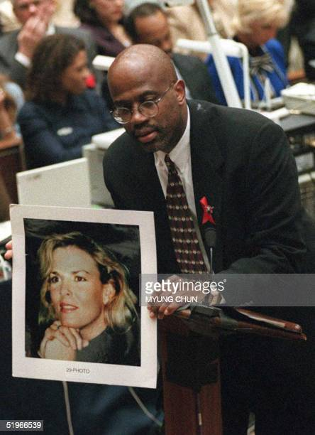 Prosecutor Christopher Darden holds a smiling portrait of murder victim Nicole Brown Simpson to contrast it with photos of a battered Nicole shown to...