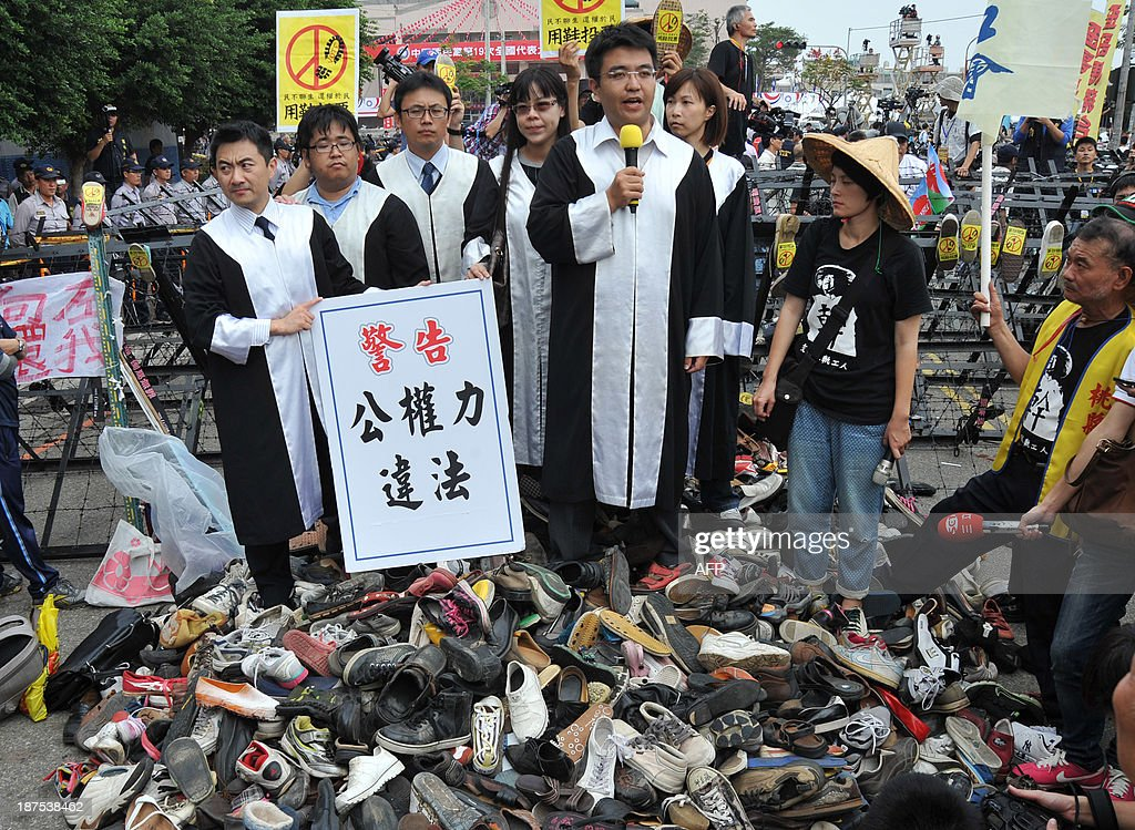 Prosecutors take part at a protest outside the national congress of the ruling Kuomintang (KMT) party in Taichung on November 10, 2013. Hundreds of angry protestors threw shoes towards riot police on November 10 as Taiwan's ruling Kuomintang party held a congress, calling for unity amid mounting discontent from the public. AFP PHOTO / Mandy
