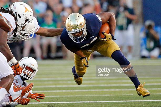 J Prosise of the Notre Dame Fighting Irish evades the tackles of the Texas Longhorns defense during the first quarterat Notre Dame Stadium on...