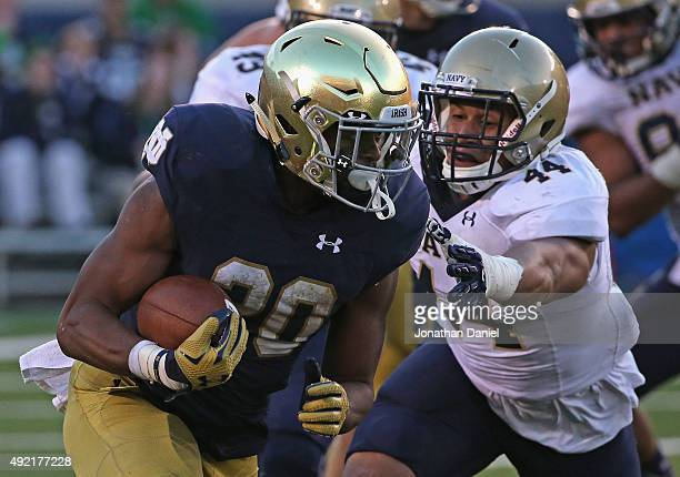 J Prosise of the Notre Dame Fighting Irish runs for a first down past Micah Thomas of the Navy Midshipmen at Notre Dame Stadium on October 10 2015 in...