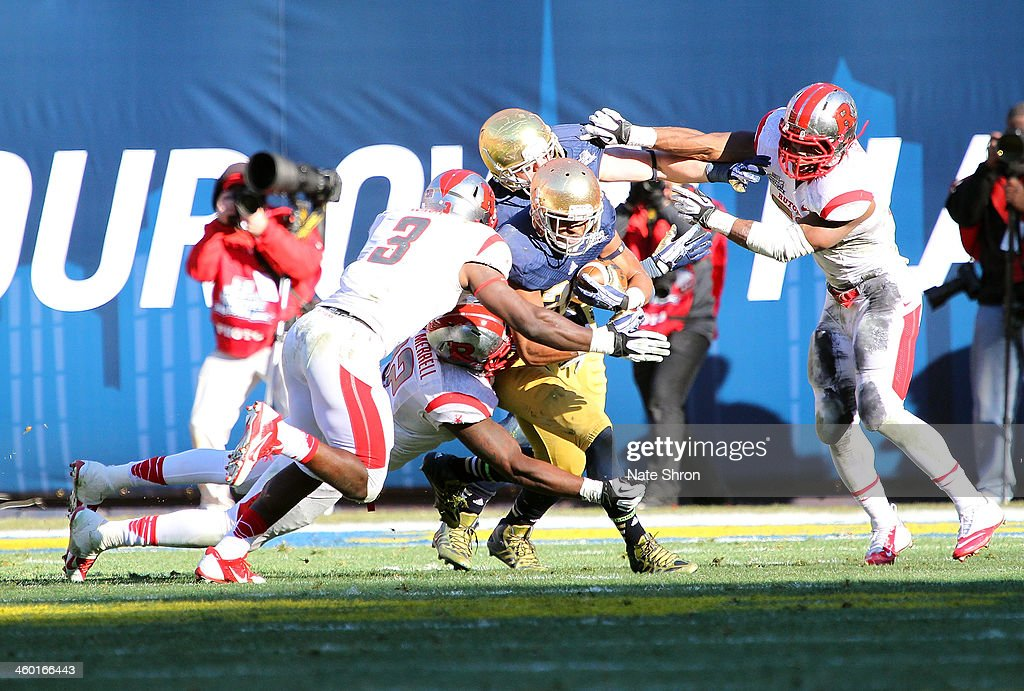 C.J. Prosise #20 of the Notre Dame Fighting Irish runs the ball against Steve Longa #3 of the Rutgers Scarlet Knights during the New Era Pinstripe Bowl at Yankee Stadium on December 28, 2013 in the Bronx Borough of New York City.