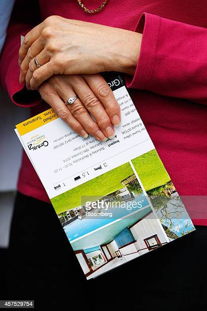 A prospective buyer holds a brochure during an auction of a property in the suburb of Roseville in Sydney Australia on Saturday Oct 18 2014 Sydneys...