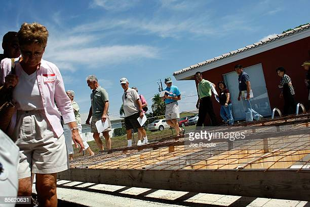 Prospective buyers walk by an empty pool as they inspect a foreclosed home while on a foreclosure boat tour with Foreclosures 'R Us realty company...
