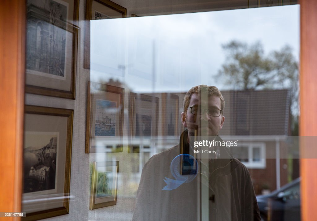 Prospective Conservative MSP for Dumfriesshire Oliver Mundell is reflected in a window of a house as he canvasses on the doorstep of a housing estate on May 4, 2016 in Dumfries, Scotland. The son of David Mundell, the Secretary of State for Scotland and the only Tory MP in Scotland, is hoping that disgruntled Labour voters and a swing to the Conservatives in the constituency he is campaigning in will lead to him taking a place in Holyrood in tomorrow's Scottish Parliament elections. As campaigning for the Holyrood election enters its last twenty four hours, recent polls suggest the Conservatives are virtually neck-and-neck with Labour in the race to be the main opposition party in Scotland.