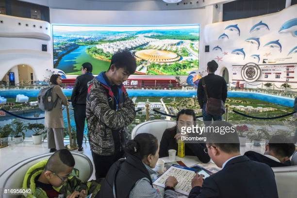 Prospective customers gather at a table to inspect building floor plans at a real estate showroom inside the Dalian Wanda Group Co Oriental Movie...