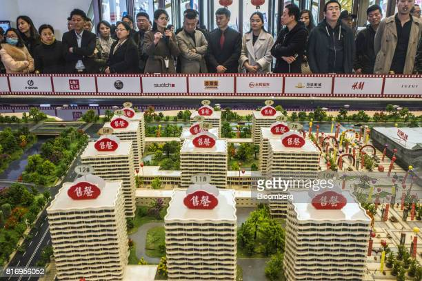 Prospective customers look at a model of the Dalian Wanda Group Co Oriental Movie Metropolis at a real estate showroom inside the project site in...