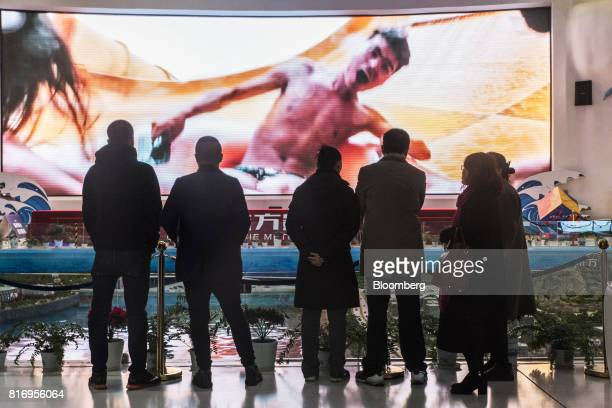 Prospective customers look at a screen displaying a film scene at a real estate showroom inside the Dalian Wanda Group Co Oriental Movie Metropolis...