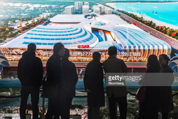 Prospective customers look at a screen displaying artist's impressions of the Dalian Wanda Group Co Oriental Movie Metropolis at a real estate...