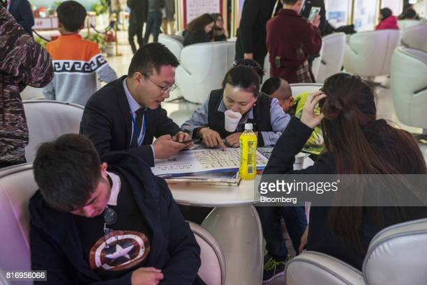 Prospective customers sit at a table while inspecting building floor plans at a real estate showroom inside the Dalian Wanda Group Co Oriental Movie...