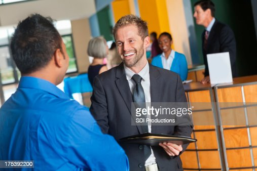 Prospective employer discussing company with businessman at job fair