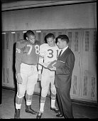 Prospective University of Pittsburgh football players no 78 Jimmy Jones and no 31 Eric Crabtree with coach Louis 'Bimbo' Cecconi in locker room...