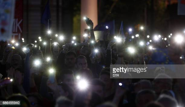 Prostesters hold their lit cell phones at the parliament buliding in Budapest on May 21 as they take part in a demonstration against tough laws...