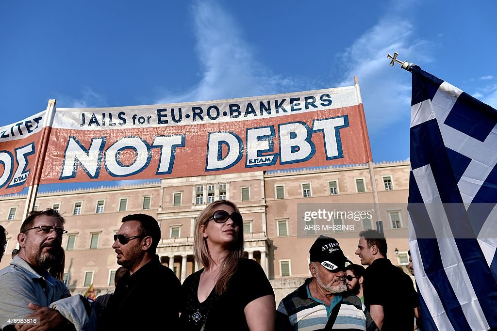 Prostestors stand below a banner reading ''No Debt'' in reference to the forthcoming referendum on bailout conditions set by the country's creditors...