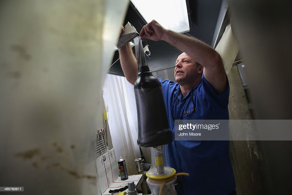 Prosthetist Edward Sliwinski pours resin while constructing a custom leg socket for a U.S. military veteran amputee at the Veterans Administration (VA), hospital on January 29, 2014 in Manhattan, New York City. The Prosthetics Center at the hospital constructs more artificial limbs then any VA hospital in the United States, both for veterans suffering combat injuries and veterans who have lost limbs following their service in the military.