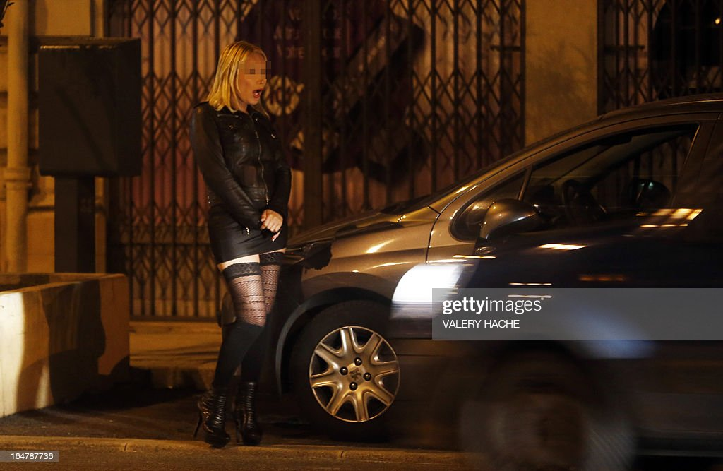A prostitute waits for a client in a street of the French southeastern city of Nice, on March 28, 2013. France's Senate will examine today a draft law aimed to abrogate the offense of soliciting clients. The bill should be adopted despite Socialist Party members dissenting on the issue.