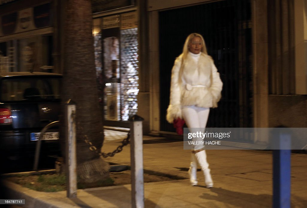 A prostitute walks in a street of the French southeastern city of Nice, on March 28, 2013. France's Senate will examine today a draft law aimed to abrogate the offense of soliciting clients. The bill should be adopted despite Socialist Party members dissenting on the issue. AFP PHOTO / VALERY HACHE