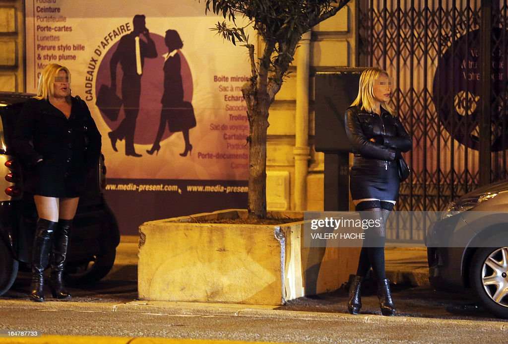 Prostitutes wait for clients in a street of the French southeastern city of Nice, on March 28, 2013. France's Senate will examine today a draft law aimed to abrogate the offense of soliciting clients. The bill should be adopted despite Socialist Party members dissenting on the issue.