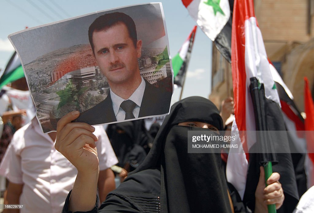 A pro-Syrian regime activist, one holding up a poster of Syrian President Bashar al-Assad, takes part in a protest against the Israeli attacks on Syria as they rally outside the United Nations offices in the capital Sanaa, on May 7, 2013. Israeli air raids on Syria at the weekend killed at least 42 soldiers, a watchdog said, fuelling international concern over a spillover of the conflict, as Damascus warned it would strike back.