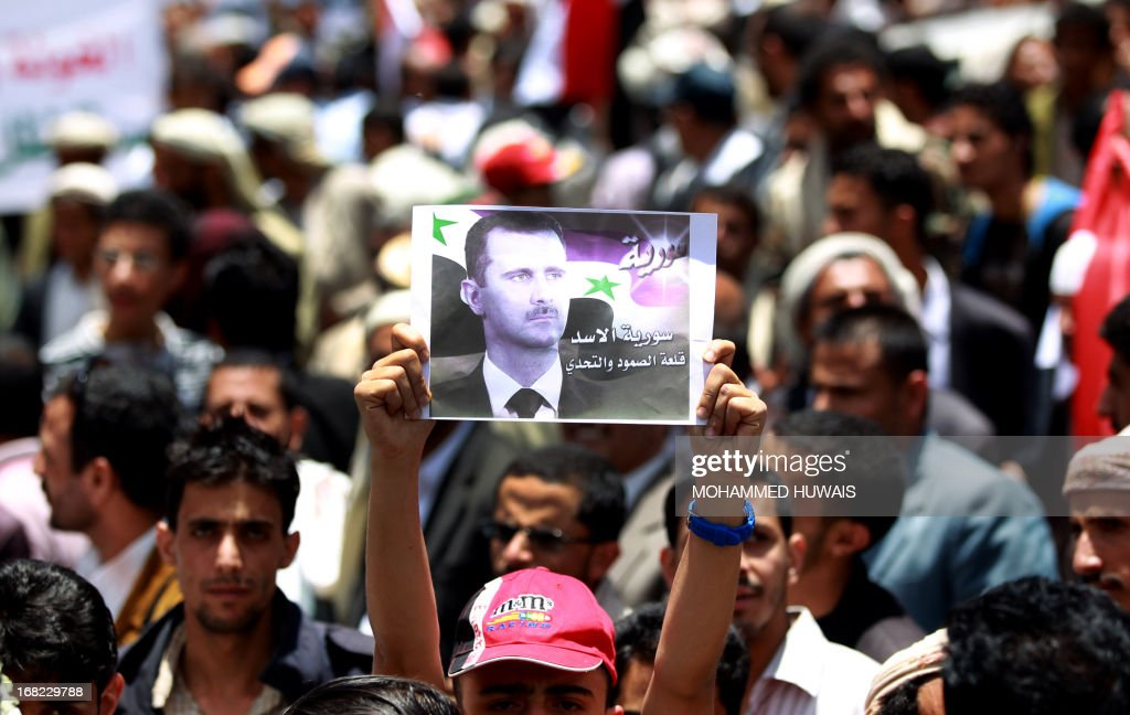 Pro-Syrian regime activists, one holding up a poster of Syrian President Bashar al-Assad, shout slogans during a march against the Israeli attacks on Syria as they rally outside the United Nations offices in the capital Sanaa, on May 7, 2013. Israeli air raids on Syria at the weekend killed at least 42 soldiers, a watchdog said, fuelling international concern over a spillover of the conflict, as Damascus warned it would strike back.