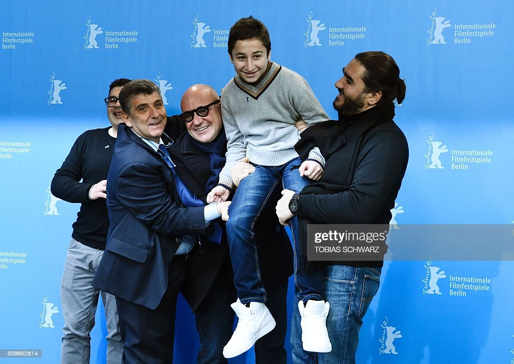 Protagonist Giuseppe Fragapane, protagonist Pietro Bartolo, Italian director Gianfranco Rosi, protagonist Samuele Pucillo and assistant director Giuseppe del Volgo pose during a photo call for the film 'Fuocoammare' (Fire At Sea) in competition at the 66th Berlinale Film Festival in Berlin on February 13, 2016. / AFP / TOBIAS SCHWARZ
