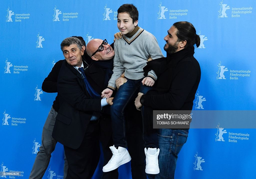 Protagonist Giuseppe Fragapane (covered), protagonist Pietro Bartolo, Italian director Gianfranco Rosi, protagonist Samuele Pucillo and assistant director Giuseppe del Volgo pose during a photo call for the film 'Fuocoammare' (Fire At Sea) in competition at the 66th Berlinale Film Festival in Berlin on February 13, 2016. / AFP / TOBIAS SCHWARZ