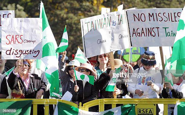 ProTaiwan protesters wave flags and signs as Chinese President His Excellency Mr Hu Jinato leaves the Auckland War Memorial Museum Auckland 27...