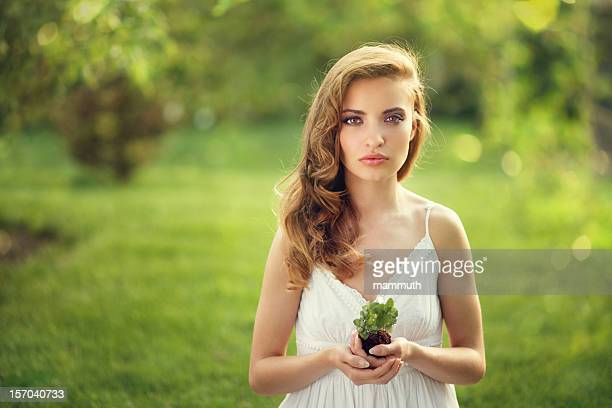 protect the nature - girl holding small plant