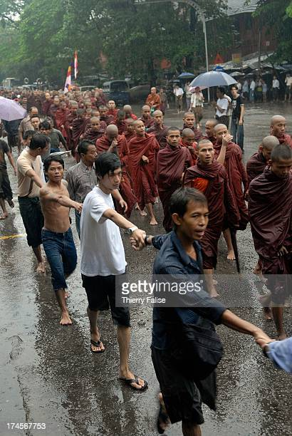 Protected by a human chain of civilian supporters Burmese Buddhist monks protesting against the military junta are marching in the streets of Rangoon