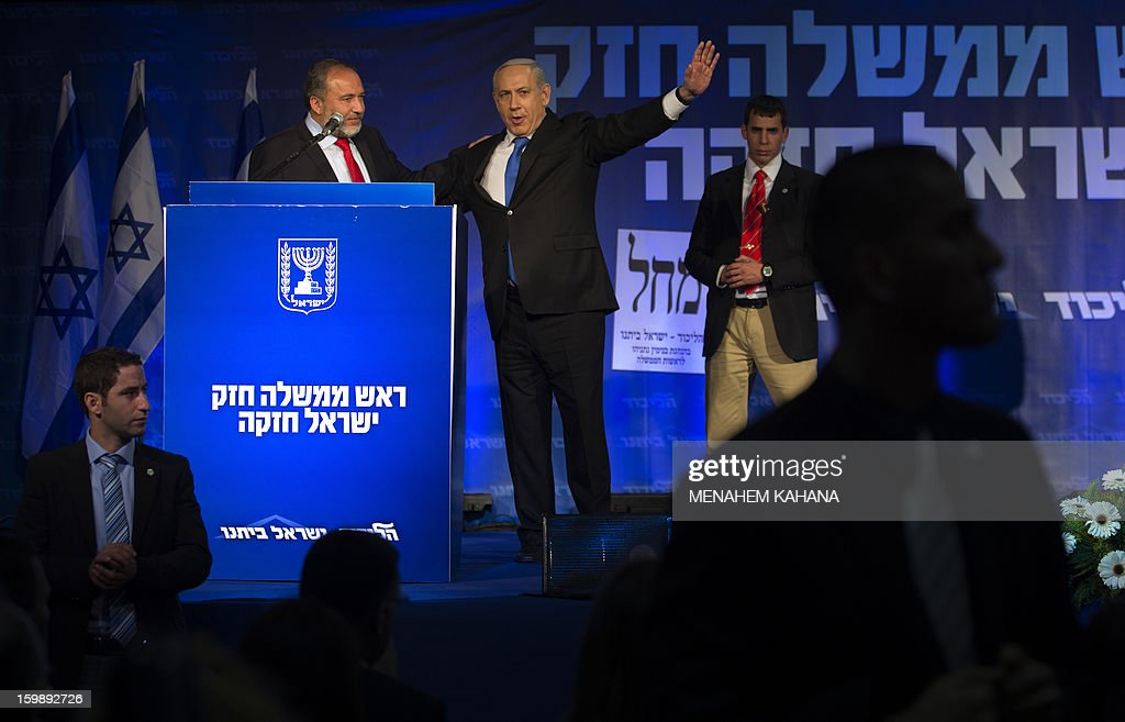 Protected by bodyguards, Israeli Prime Minister Benjamin Netanyahu (C) and ultra-nationalist Avigdor Lieberman (L) of the Likud-Beitenu coalition wave to supporters at the party headquarters in Tel Aviv early on January 23, 2013 after their Likud-Beitenu list won the Israeli general elections. Netanyahu said it was necessary to form the 'broadest possible government' after his Likud-Beitenu list won a narrow election victory, with the centrist Yesh Atid in second place. AFP PHOTO/MENAHEM KAHANA