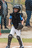 Little league catcher in protective mask and chest pad looking alert toward the next play at home.