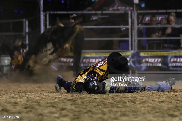 A protection athletes watches his partner being rammed by the bull as he lies over a motionless Jay Borghero of Rockhampton to protect him after he...