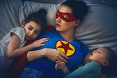 Adorable little children girls are napping in the bed with their mom. Quiet sleep under the protection of the mother superhero.
