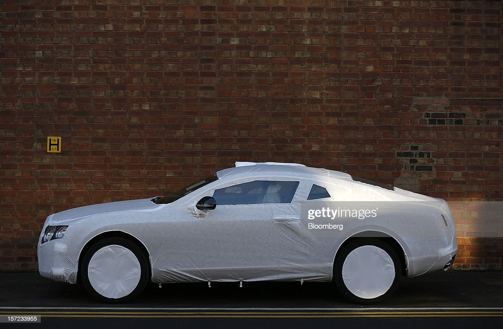 A protective cover sits on a completed Bentley Continental automobile parked outside the workshop at the Bentley Motors Ltd. plant in Crewe, U.K., on Thursday, Nov. 29, 2012. Consumer spending and exports propelled the U.K. economy to its fastest growth since 2007 in the third quarter as the Olympics and a post-Jubilee rebound saw household expenditure rise the most in more than two years. Photographer: Simon Dawson/Bloomberg via Getty Images