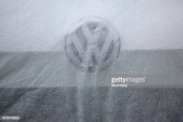 A protective cover sits on a new Volkswagen Golf automobile outside a Volkswagen AG showroom in Berlin Germany on Wednesday July 26 2017 Carmakers'...