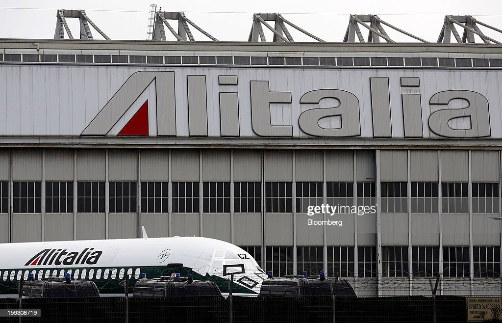 Protective covers sit on the cockpit windows of an Alitalia SpA aircraft parked outside a hangar at Fiumicino airport in Rome, Italy, on Friday, Jan. 11, 2013. Former Italian Prime Minister Silvio Berlusconi's economic adviser said the European debt crisis has left his country's companies vulnerable to takeovers by foreign rivals and urged the government to prepare defences. Photographer: Alessia Pierdomenico/Bloomberg via Getty Images