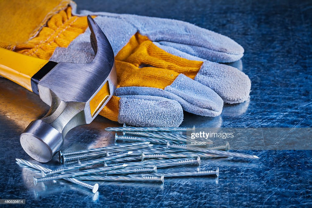 Protective glove variety of metal nails and claw hammer on : Stock Photo