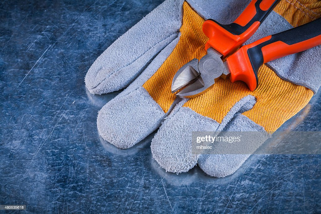 Protective gloves with nippers on scratched vintage metallic bac : Stock Photo