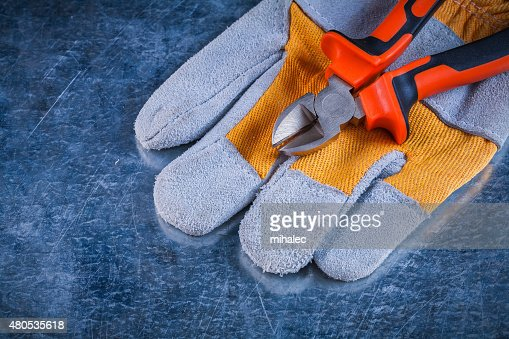 Protective gloves with nippers on scratched vintage metallic bac : Bildbanksbilder