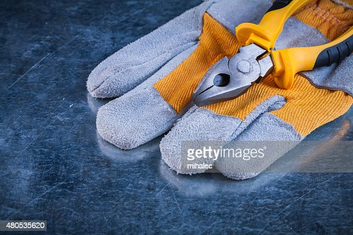 Protective gloves with pliers on scratched metallic background c : Stockfoto