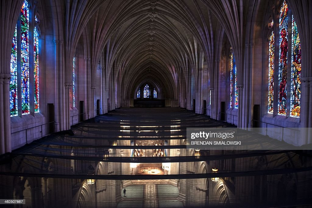 Protective netting is seen midway between the stained glass windows and the floor protecting people from falling debris at the National Cathedral on January 13, 2014 in Washington. The National Cathedral is still undergoing repairs related to the 2011 earthquake that affected the area. AFP PHOTO/Brendan SMIALOWSKI