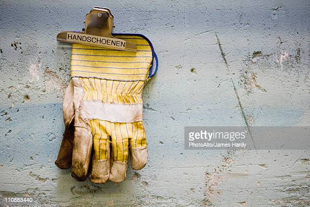 Protective work gloves held up by a binder clip on wall